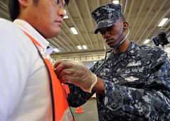 Hospital Corpsman 2nd Class Shuntae Heck performs a physical assessment of a mock evacuee during a non-combatant evacuation operation (NEO) aboard the amphibious assault ship USS Bonhomme Richard (LHD 6). (U.S. Navy photo by Mass Communication Specialist 1st Class N. Ross Taylor)
