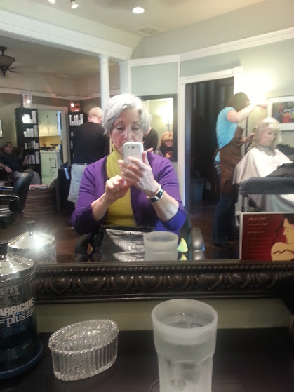 DarkEmeralds in a hair salon mirror, wearing a yellow shirt and a purple cardigan