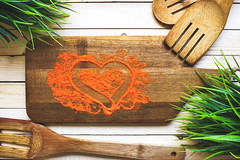 Spices in the form of heart on a wooden board near…