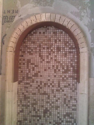 Travertine tile arch niche and mosaic background