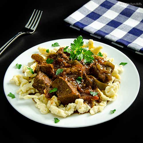 Hungarian Beef Paprika Stew (Pörkölt) on plate with Spätzle