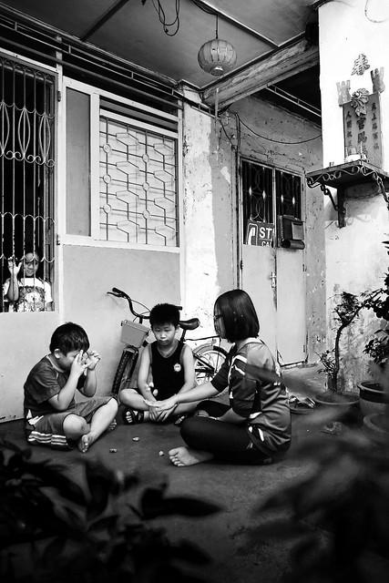 "Playing ""batu seremban"" in the five-foot way"