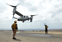 Aviation Boatswain's Mate (Handling) 3rd Class Barry Swanson recovers a Marine Corps MV-22 Osprey tiltrotor aircraft on the flight deck of the forward-deployed amphibious assault ship USS Bonhomme Richard (LHD 6), March 14 in the East China Sea. (U.S. Navy photo by Mass Communication Specialist 2nd Class Jerome D. Johnson)