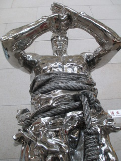 Silver statue of a man, standing dramically posed with rope around his waist.