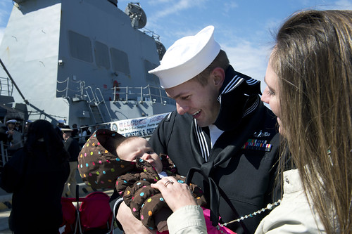 A Sailor meets his new baby after nine months at sea