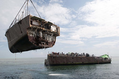 The bow of the mine countermeasure ship Ex-Guardian (MCM 5) is removed by the crane vessel M/V Jascon 25 during operations March 26. (U.S. Navy photo by Mass Communication Specialist 3rd Class Kelby Sanders)