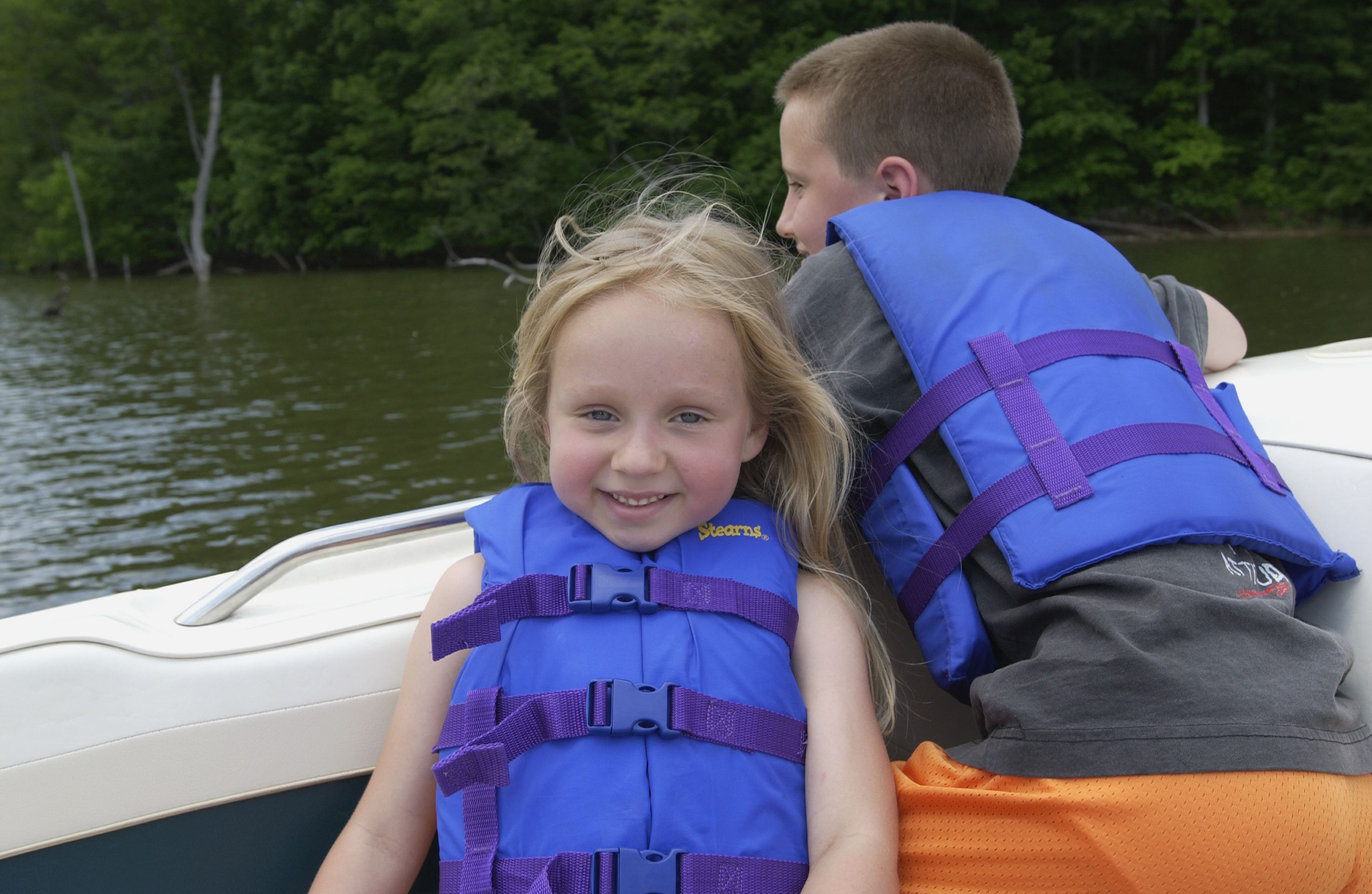 Children are wearing life jackets on boat