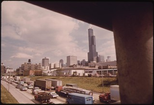 Heavy Traffic On The Dan Ryan Expressway In Chicago Illinois. The Tall Building In The Background Is The Sears Tower, 110 Stories High And The World's Tallest At The Time It Was Built, 10/1973