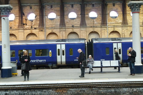 picture of people using the mobile phones on york railway station.