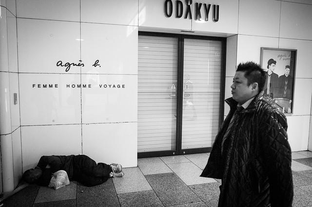 Homeless in Odakyu mall, Shinjuku, Tokyo. Image captured with snap focus at the man walked pass.