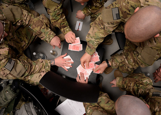 Airmen play cards while waiting for the plane