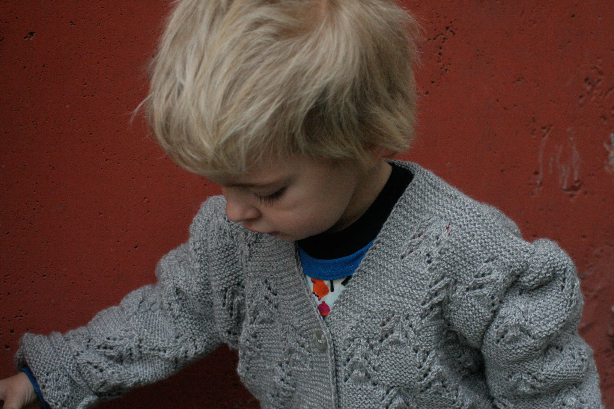 Grey cardigan, orange wall