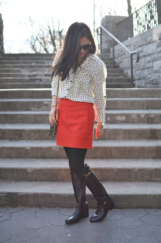 black & white polka dot top blouse, red wool skirt, and black riding boots
