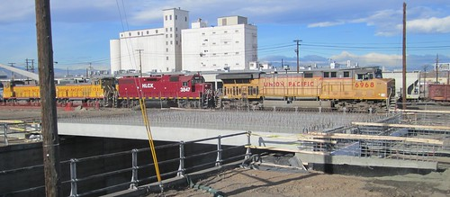 Photo of commuter rail bridge girders placed over the 38th Street underpass near Blake Street, Union Pacific train in background