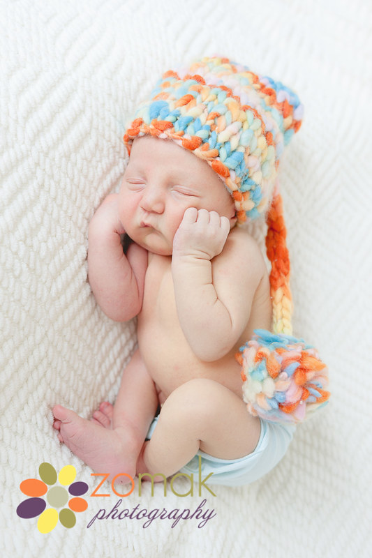 Cuddly and sweet baby boy sleeps with a soft knitted hat during his newborn photos.