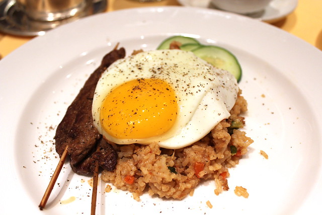 Nasi Goreng Indonesian spiced rice with chicken, fried egg and cucumber accompanied by beef satays and peanut dip