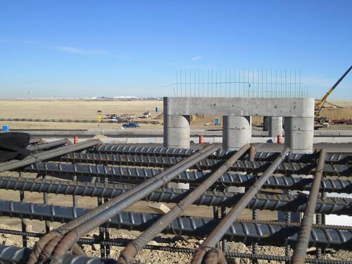 Photo of commuter rail bridge piers being built over E 470 toll road near Denver International Airport