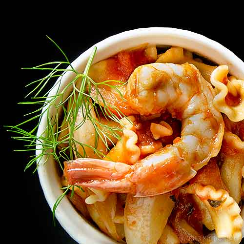 Pasta with Shrimp and Fennel in white ramekin, overhead view on black