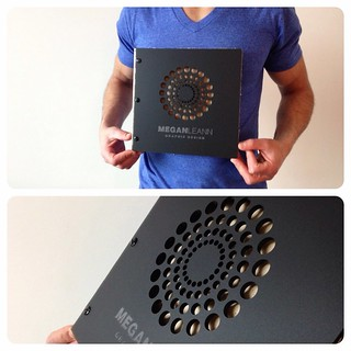Custom small square graphic design portfolio book in matte black acrylic with engraving and cut-out treaments