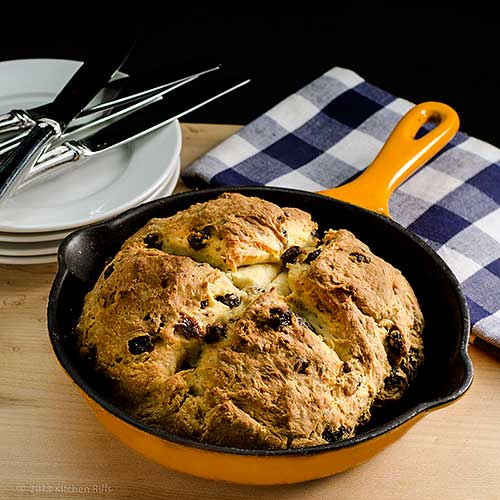 Irish Soda Bread in Skillet with plates and napkin in background
