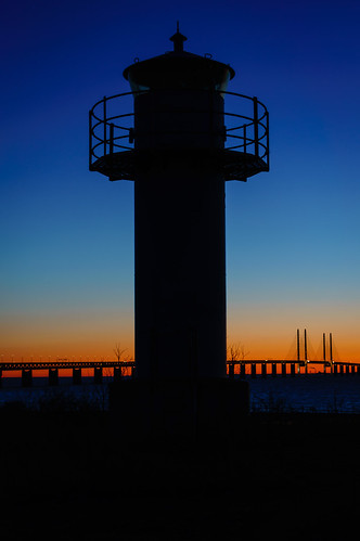 Lighthouse silhouette by the bridge