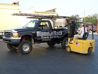 Man Loading Palletized Block On Heavy-Duty Truck Bed Cover On Company Pickup Truck