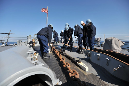 Sailors aboard USS Lassen remove a pelican hook on the anchor chain during sea and anchor operations