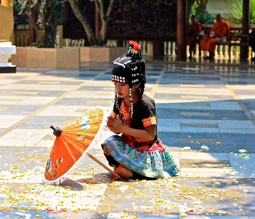 a young Hmong girl performing in front of Wat Phra That Doi Suthep