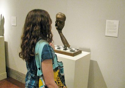 Philosophy student admiring an art sculpture.