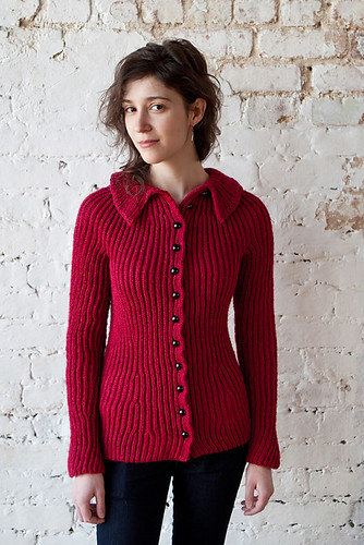 A handknit raspberry-colored ribbed and fitted buttoned cardigan