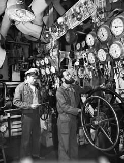 Two unidentified men in the control room of a boat / Deux hommes non identifiés dans la salle des commandes d'un navire