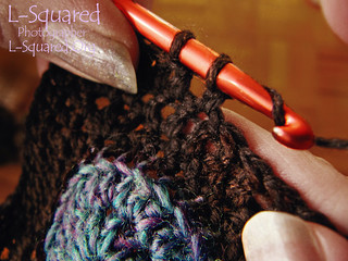 Close up of my hands as I work with brown yarn and an orange metal crochet hook; I'm in the midst of adding an edging of double  crochet stitches around a blue crocheted disk.
