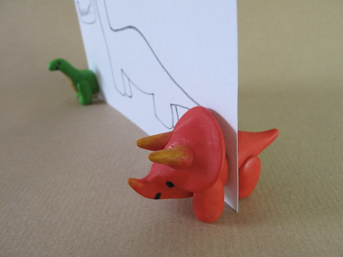Fimo dinosaurs holding a card