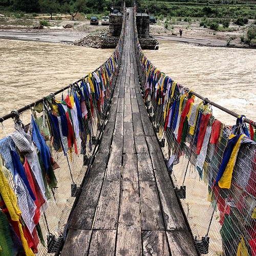 Daydreaming. #bhutan #travel #bridge #flags #river #himalayas