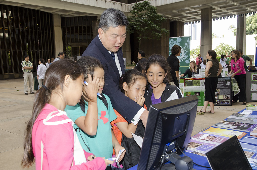 <p>State Representative Mark Takai and young friends play a game hosted by the UH Cancer Center.</p>