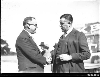 Two men, including Stanley S Crick, shaking hands at a Movietone event