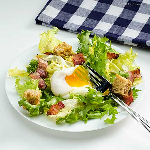 Salade Frisée aux Lardons on Plate with Fork Breaking into Poached Egg
