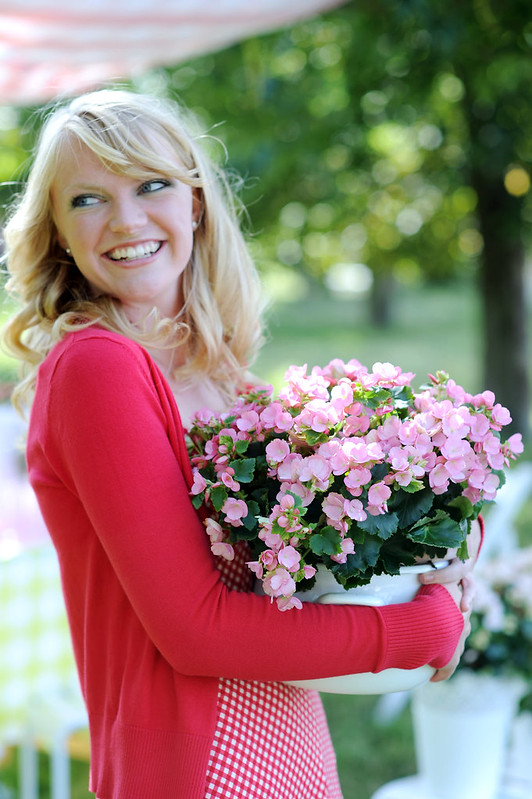 Glimlachende vrouw houdt kamerplant betulia vast