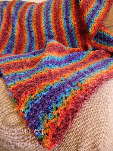 Completed blanket draped over a chair - it is made of stitches that look like tiny shells and the variegated, self-striping yarn is dark red, bright orange, school-bus yellow, bright green, turuoise and violet.