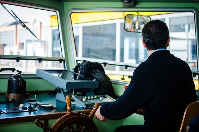A vaporetto driver steers the water bus through Venice's Grand Canal.