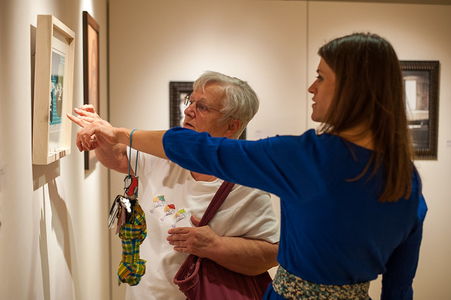 New Media student Sarah Swoverland talks about her work with a visitor to the IU Kokomo art gallery's annual student show.