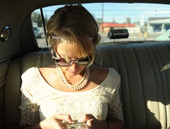 Jessie texting friends in her cream colored lace day frock, sun, sunglasses and pearls, wedding day, from the back seat of her fiancé Chris's classic car, Fairbanks, Alaska, USA