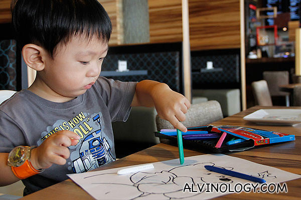 Asher colouring with crayons on paper, with material provided by the nice staff at Charly T
