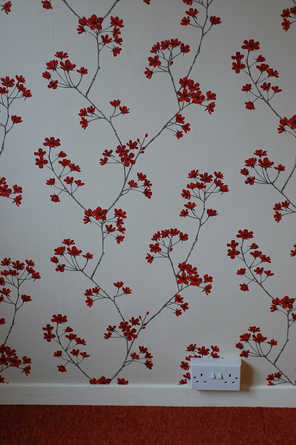 Wallpaper with a quince blossom pattern, red on white.