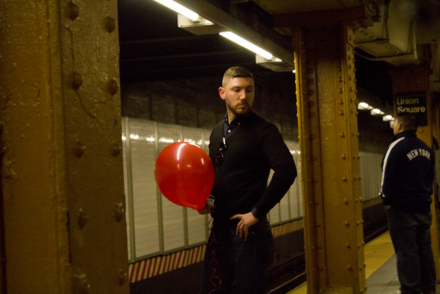Man on Subway with Red Balloon