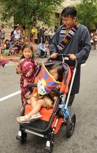 Happy Tibetan family man, his daughers, a toddler under the Tibetan flag, and his lovely young daughter in a formal silk gown, Happy Birthday to His Holiness the Great Dalai Lama, Washington D.C., USA by Wonderlane