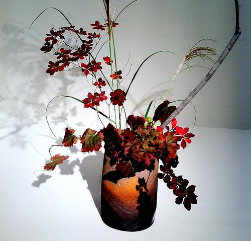 Japanese ikebana with several different plants in a yakimono container
