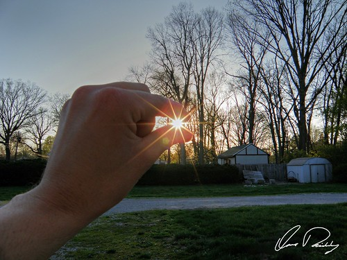 holding sun sunlight sunset pinch pinching between finger fingers