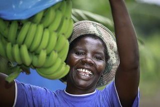 A woman smiles and holds a bunch of bananas