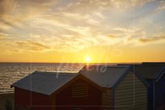 Sunset behind Brighton beach boxes